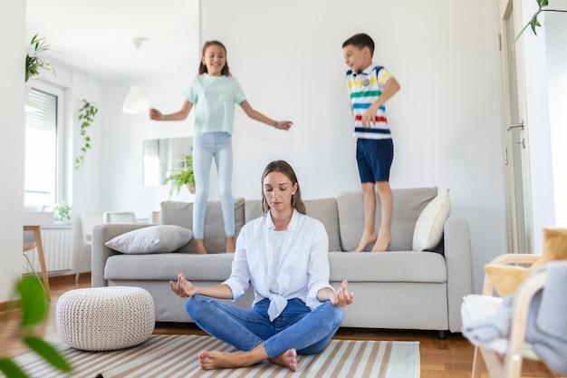 Jeune mère aux yeux fermés méditant dans une pose de lotus sur le sol en essayant de sauver l'harmonie intérieure tandis que des enfants excités sautent sur un canapé et crient dans un salon spacieux et lumineux