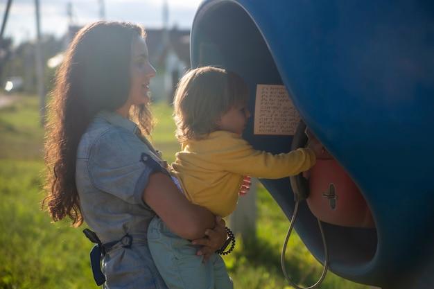 Jeune mère et bébé appellent sur un téléphone fixe dans la cabine téléphonique du village en été. marcher avec la famille journée ensoleillée d'été au soleil. orientation artistique
