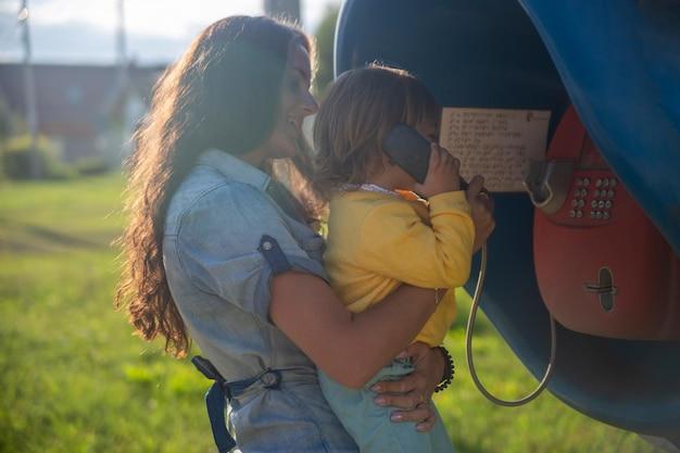Jeune mère et bébé appellent sur un téléphone fixe dans la cabine téléphonique du village en été