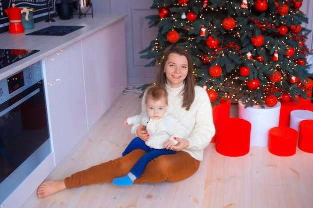Jeune mère avec bébé fils dans une cuisine blanche avec arbre de noël rouge.