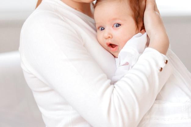 Jeune mère et bébé nouveau-né dans une chambre blanche