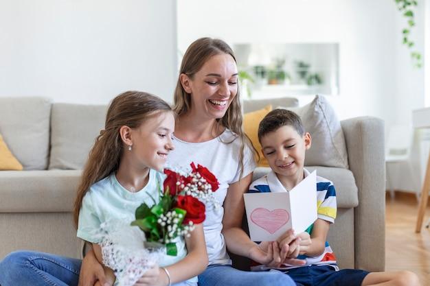 Jeune mère avec un bouquet de roses rit, serrant son fils dans ses bras, et «fille joyeuse avec une carte et des roses félicite maman lors de la célébration des vacances à la maison. fête des mères