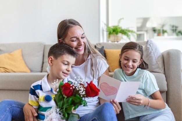 Une jeune mère avec un bouquet de roses rit, serrant son fils dans ses bras, et une fille pleine de bonne humeur avec une carte et des roses félicite maman pendant les fêtes de fin d'année dans la cuisine à la maison. fête des mères