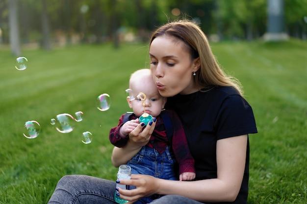 Jeune mère caucasienne gonfle des bulles de savon avec son petit fils dans un parc par une journée d'été ensoleillée.