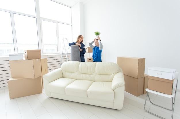 Jeune mère célibataire mignonne et son fils sont heureux du déménagement dans une nouvelle maison tenant un pot de légumes verts et