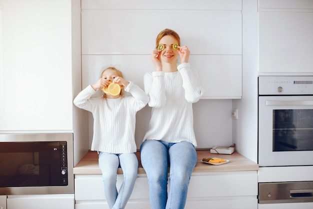 Jeune mère avec des cheveux clairs en dentelle blanche et un pantalon bleu jeans assis à la maison