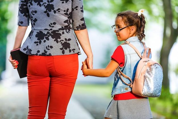 Une jeune mère conduit sa fille à l'école