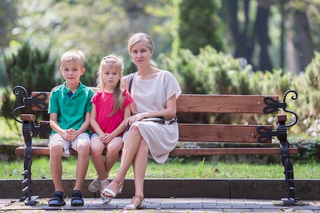 Jeune mère et deux enfants garçon et fille s'amuser ensemble sur un banc dans le parc d'été.