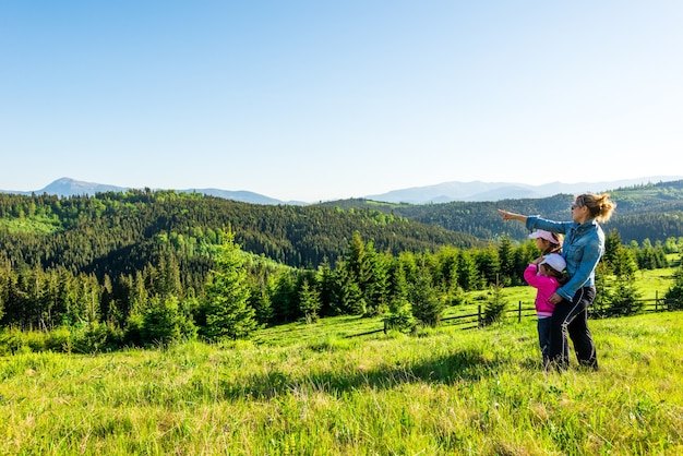 Jeune mère et deux petites filles voyageurs se tiennent sur une pente avec une vue magnifique sur les collines couvertes de forêt dense de sapins contre le ciel bleu sur une chaude journée d'été ensoleillée
