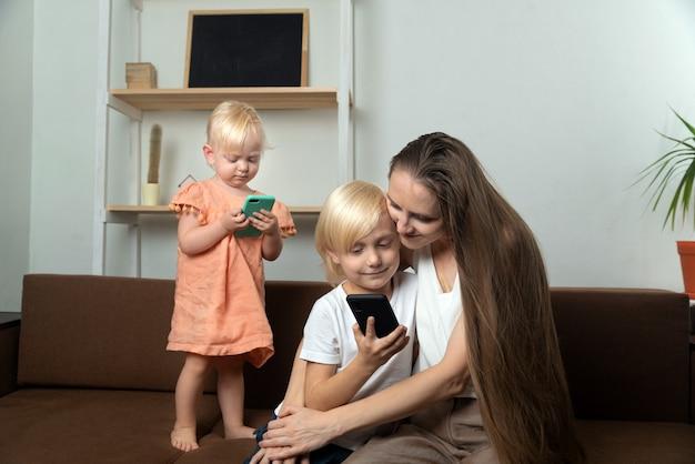 Jeune mère et deux petits enfants avec des téléphones à la main. maman embrasse son fils et regarde son téléphone.