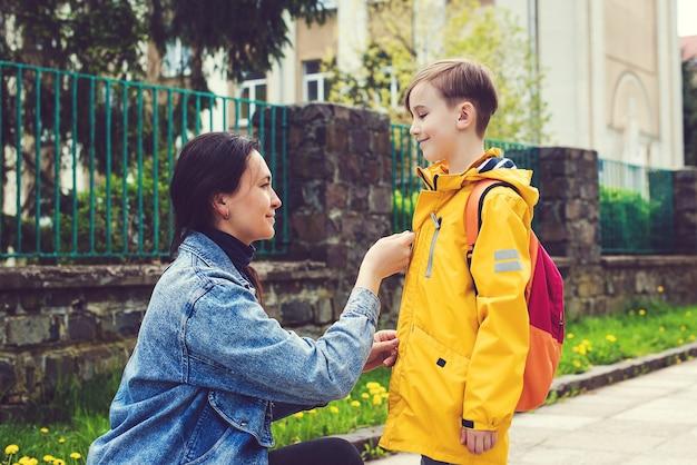 Jeune mère disant au revoir à son petit fils près de l'école. femme et garçon avec sac à dos derrière le dos. début des cours. premier jour à l'école. mère emmenant son fils à l'école.