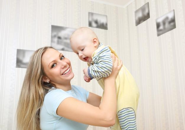 Jeune mère embrassant bébé à la maison