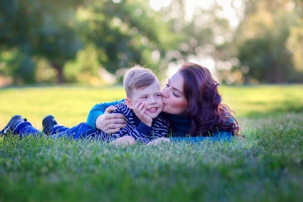 Jeune mère embrasse et embrasse le fils allongé sur une herbe dans le parc