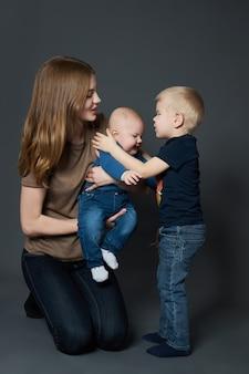La jeune mère embrasse et embrasse son petit fils. une femme tient un enfant dans ses bras