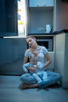 Jeune mère endormie assise dans la cuisine avec son bébé à côté du réfrigérateur