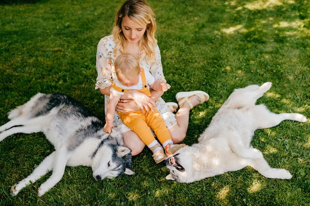 Jeune mère avec enfant et deux chiens assis dans l'herbe verte