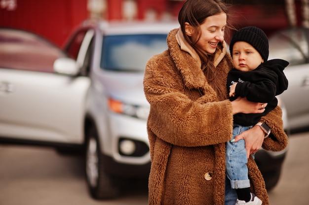 La jeune mère et l'enfant se tiennent près de leur voiture suv. concept de conduite de sécurité.