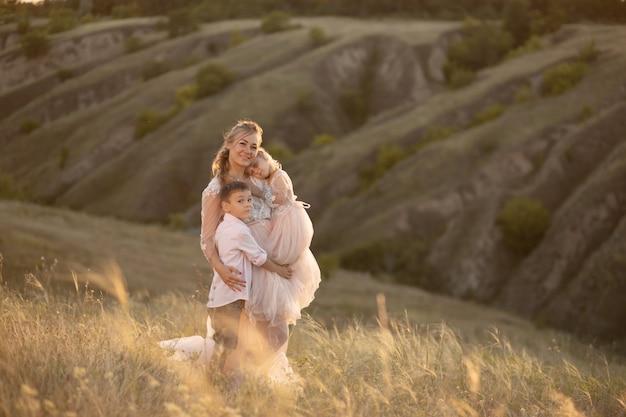 Une jeune mère avec des enfants se promène dans un champ au coucher du soleil.