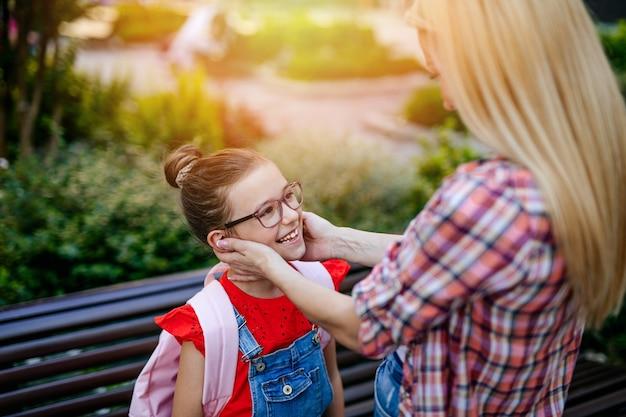 Jeune mère étreignant sa petite fille dans la cour d'école. retour au concept de l'école.