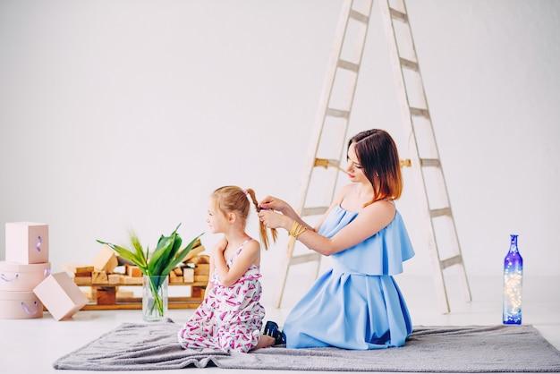Une jeune mère faisant la coiffure pour sa fille. belle mère avec sa petite fille.