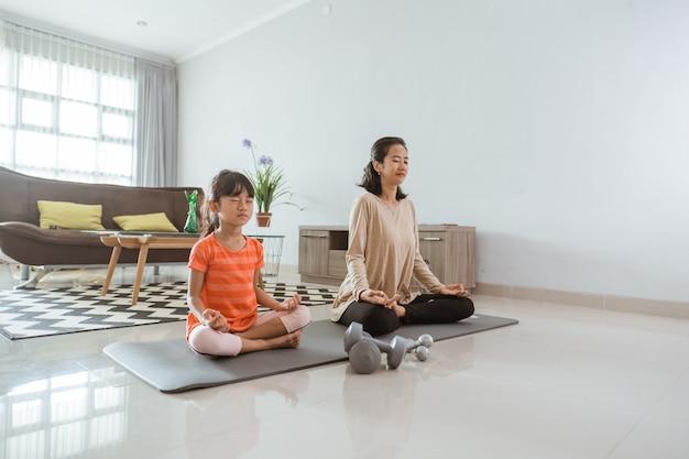 Jeune mère faisant des exercices d'yoga à la maison avec sa fille ensemble