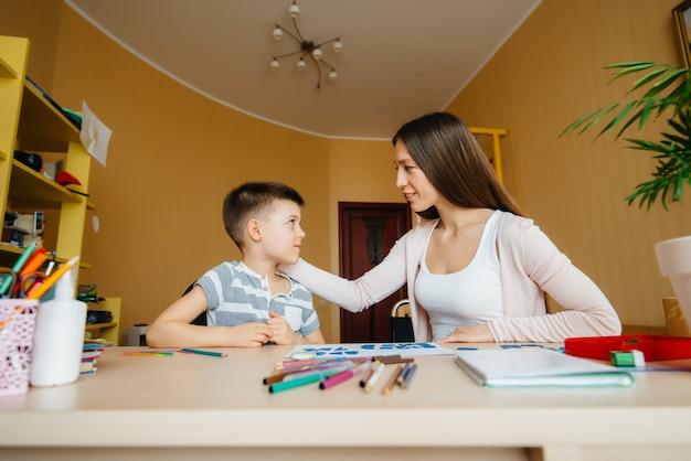 Une jeune mère fait ses devoirs avec son fils à la maison. parents et formation
