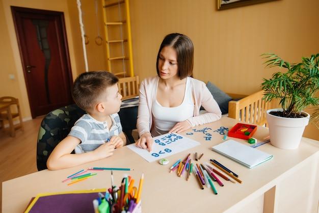Une jeune mère fait ses devoirs avec son fils à la maison. parents et formation.