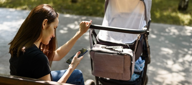 Jeune mère, femme avec poussette avec smartphone en mains assis sur un banc de parc