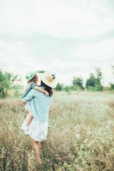 La jeune mère et fille sur l'herbe verte