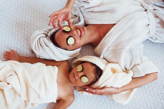 Jeune mère et fille positive avec une serviette sur la tête allongée sur le lit avec du concombre.