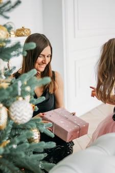 Jeune mère et fille en robes de soirée se donnent des cadeaux sur l'arbre de noël