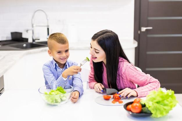 Jeune mère avec fils garçon cuisine salade maman en tranches légumes légumes fils donner à la mère dégustation de salade. famille heureuse, cuisiner, nourriture, jouissance, style de vie, cuisine