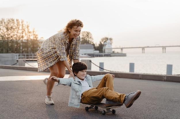 Jeune mère et fils s'amusant avec une planche à roulettes dans la rue