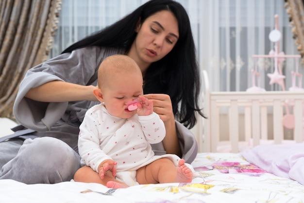 Une jeune mère habille un bébé agité dans une chambre le matin.