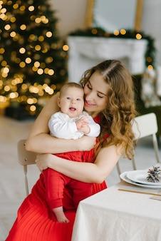 Une jeune mère heureuse dans une robe rouge tient son fils dans ses bras contre les lumières de noël dans le salon