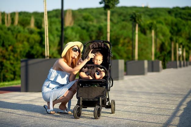 Une jeune mère heureuse marche avec son bébé dans une poussette dans le parc en été au soleil couchant et sourit tout en s'amusant à pointer au loin