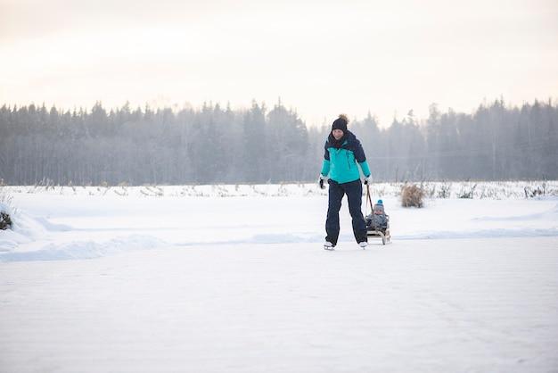 Jeune mère heureuse et petit bébé garçon fils de traîneau sur le lac d'hiver enneigé ensemble
