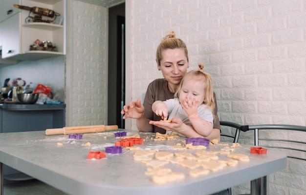 Une jeune mère heureuse et sa petite fille préparent ensemble de délicieux biscuits assis à la table