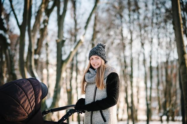 Une jeune mère heureuse se promène avec une poussette et un bébé dans un parc d'hiver