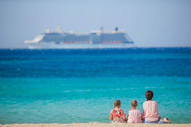 Jeune mère heureuse et ses filles adorables à la plage exotique sur une journée ensoleillée