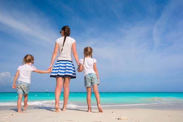 Jeune mère heureuse et ses filles adorables s'amusant à la plage exotique sur une journée ensoleillée