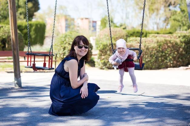 Jeune mère et jolie petite fille souriante se balançant dans le parc d'été