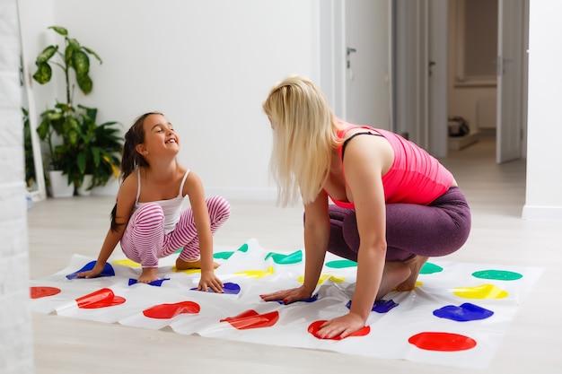 Jeune mère jouant au twister avec ses enfants. joyeuse famille à la maison. famille heureuse s'amuser ensemble.