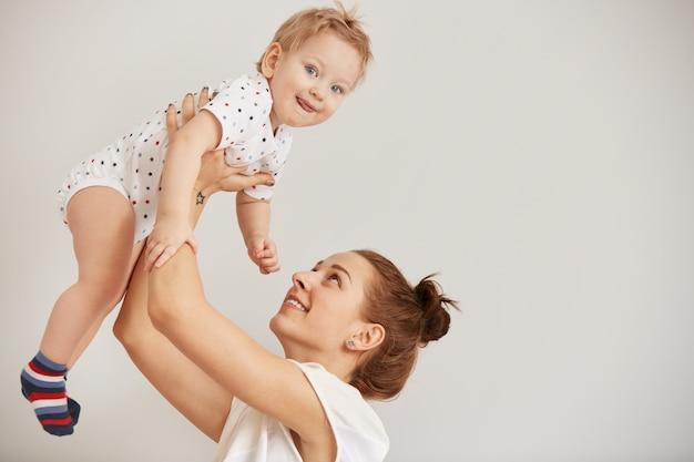 Jeune mère jouant avec son petit bébé sur le lit