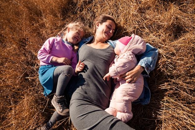 Une jeune mère joue ses filles et profite de la nature à l'arrière-plan d'un paysage de champs en automne. le concept de loisirs en plein air et de famille en automne.