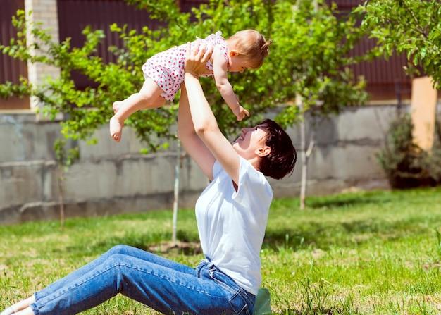 Jeune mère joue avec son bébé sur l'herbe dans le parc. maman et bébé