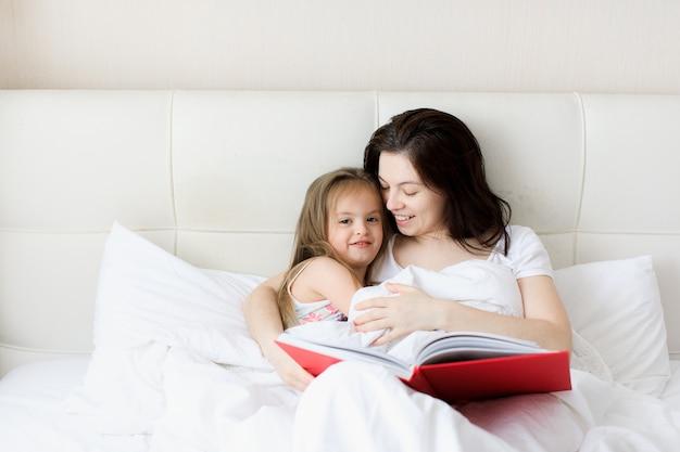 Jeune mère lit un livre au lit à son enfant