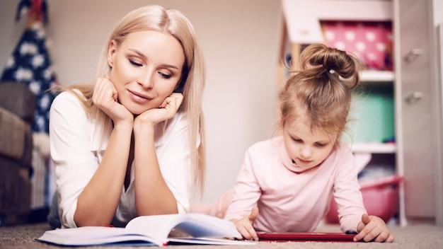 Jeune mère lit un livre à la maison allongé sur le sol à la maison avec sa fille