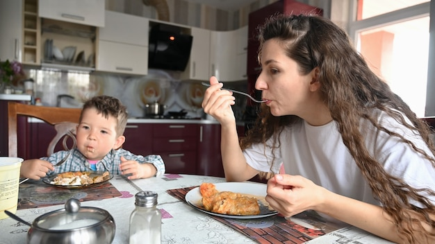 Jeune mère mangeant dans la cuisine assise à table.