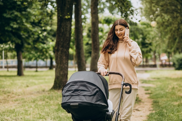 Jeune mère marchant avec landau dans le parc